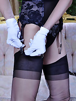 Sexy lady in hair-curlers rolls up barely black stockings with gloved hands